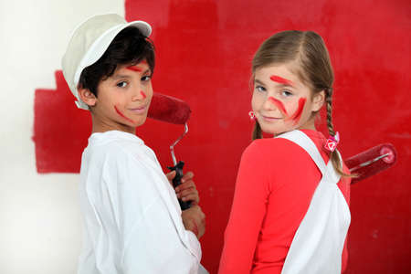 Children painting a wall red photo
