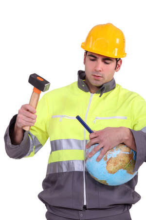 down beat: Man using hammer and chisel on globe