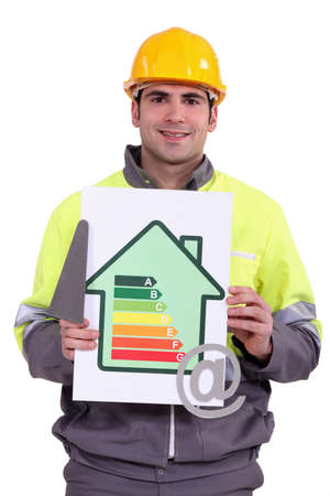 emissions: A construction worker holding a trowel, an energy efficiency rating sign and the at symbol Stock Photo
