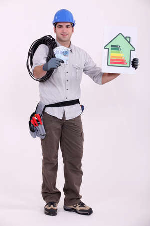cabling: Tradesman holding a wad of money and an energy efficiency rating sign Stock Photo