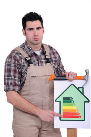 Carpenter nailing energy rating poster to wood photo