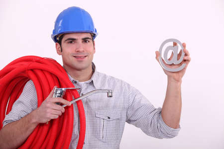 times new roman: Man holding tap cable and at symbol