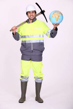 Labourer holding a globe and a pickaxe photo