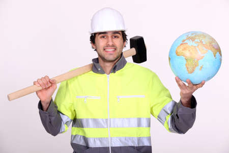 Tradesman holding a mallet and a globe photo