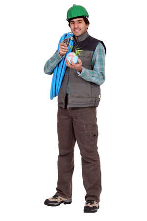 cabling: Worker holding a mini globe and cabling Stock Photo