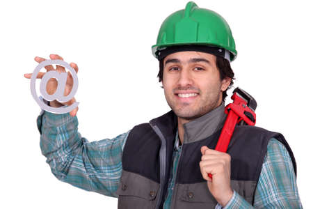 A handyman holding a at sign. photo