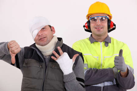 Healthy construction worker standing next to an injured man photo