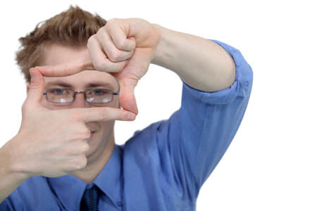 Young man using his fingers to frame his glasses photo