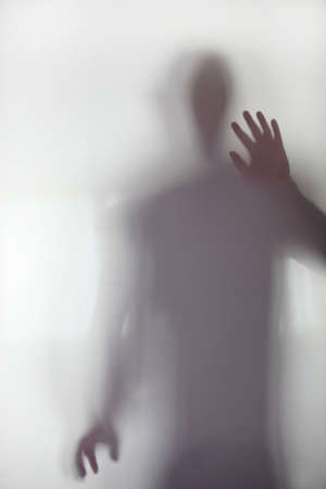 with light shadow: Person stood behind frosted glass Stock Photo