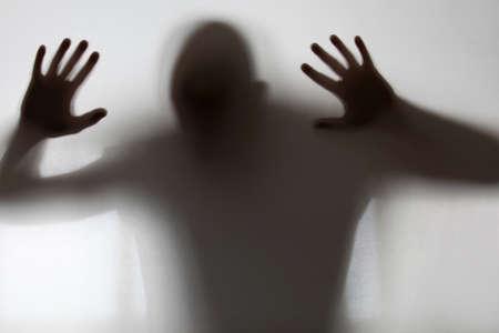 gefangener: Schattenhafte Gestalt hinter Glas gefangen