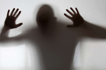 Schimmige figuur gevangen achter glas