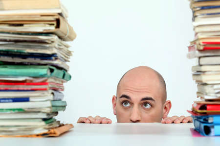 Man staring nervously at piles of folders photo