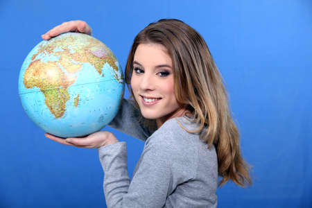 Attractive young woman holding a globe photo