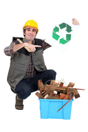 Tradesman kneeling next to a bin and holding up the recycling symbol photo