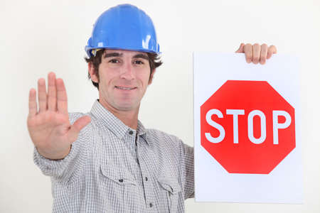 Builder holding stop sign photo