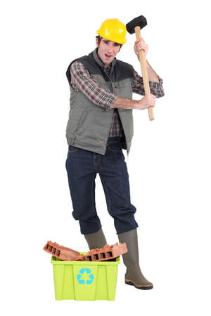 Frustrated tradesman holding a mallet and standing behind a recycling bin photo