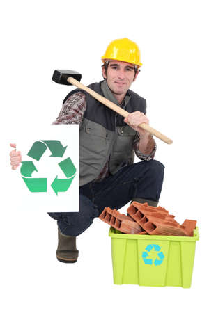 hunker: portrait of bricklayer showing recycling logo Stock Photo