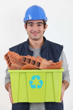 young bricklayer carrying recycling tub full of red bricks photo