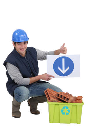 Tradesman holding a sign pointing to a recycling bin photo