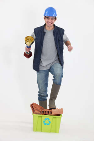 acquirement: craftsman holding a golden cup and walking over bricks Stock Photo