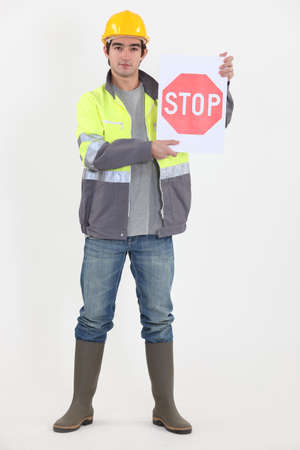 directing: A road worker holding a stop sign. Stock Photo