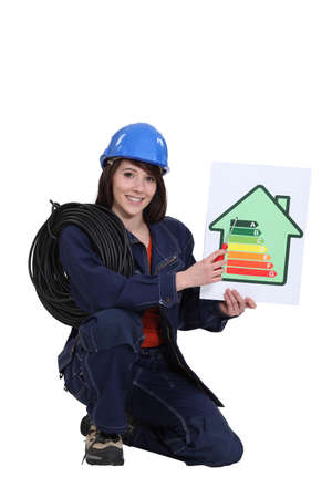Female electrician kneeling whilst holding an energy rating poster Stock Photo - 13867880