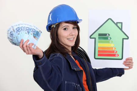 Tradeswoman holding up an energy efficiency rating chart and a wad of money photo
