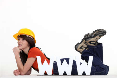 Female builder laying by large WWW letters photo