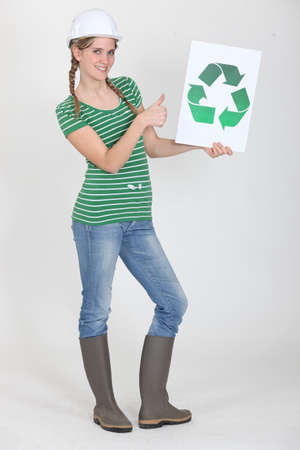 female apprentice holding recycling logo photo