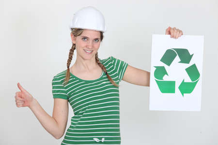 Female construction worker with a recycle sign photo
