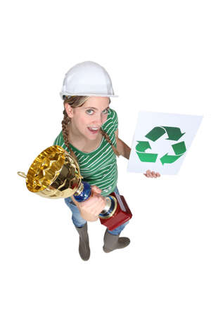woman holding a cup and a sign with recycling symbol photo