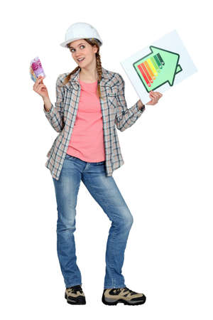pricey: Tradeswoman holding up an energy efficiency rating chart and a wad of money Stock Photo