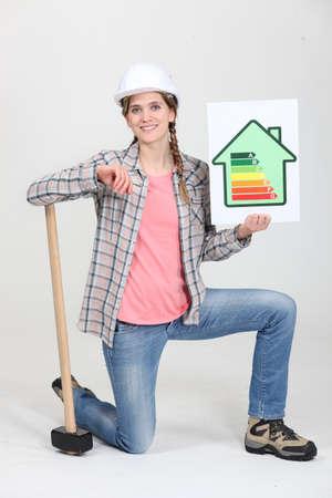 sledge hammer: A female construction worker promoting energy savings.