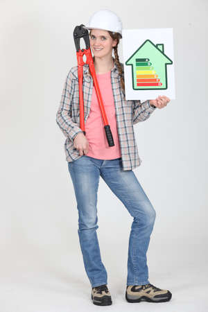 Tradeswoman holding oversized pliers and an energy efficiency rating sign Stock Photo - 13868676