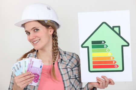 energy ranking: Woman holding energy score card and cash Stock Photo