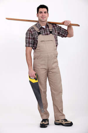 Carpenter carrying a plank of wood and a saw Stock Photo - 13868648
