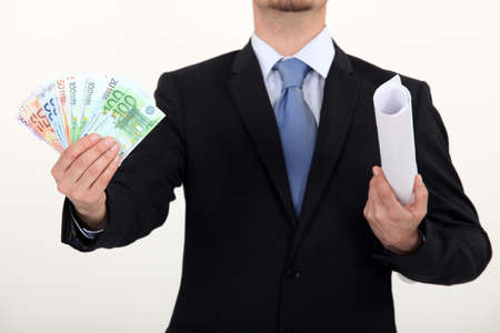 Businessman holding plans and a pile of cash