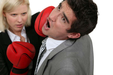 battered: blonde businesswoman boxing a colleague Stock Photo