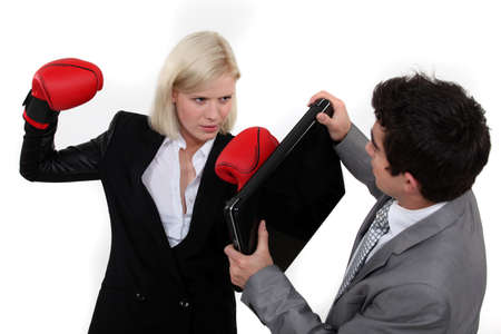 Woman with boxing gloves attacking colleague photo