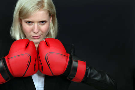 Businesswoman wearing boxing gloves photo
