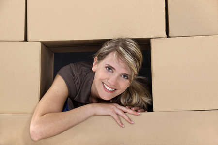 boxed: Woman surrounded by cardboard boxes Stock Photo
