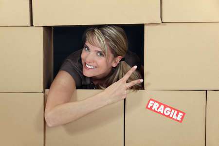Woman in a wall of cardboard boxes photo