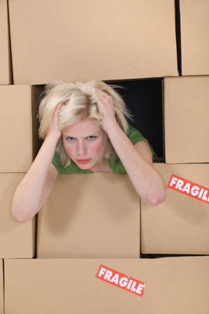 Stress blond woman amongst boxes photo