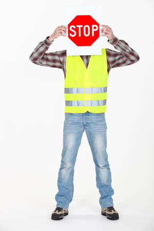 Builder covering face with stop sign photo