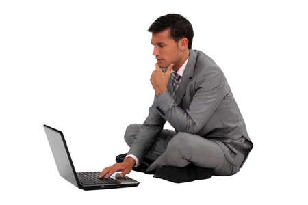 cross ties: Businessman sitting cross legged with a laptop Stock Photo