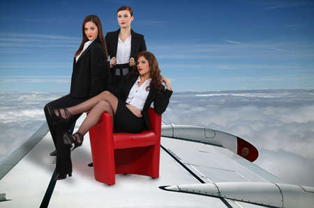 sexy businesswomen flying on a plane wing Stock Photo - 13868087