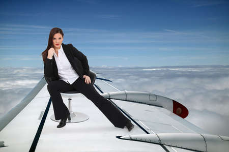 Smart woman sitting on the wing of an airplane photo