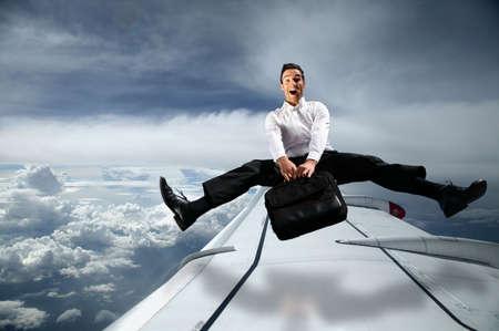 jambes �cart�es: homme sac de transport dans le ciel au-dessus avion avec les jambes �cart�es