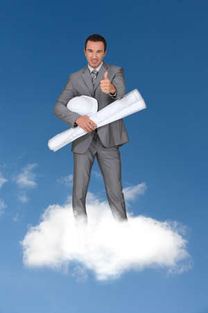 man wearing grey suit standing on cloud with rolled paper and hard hat photo