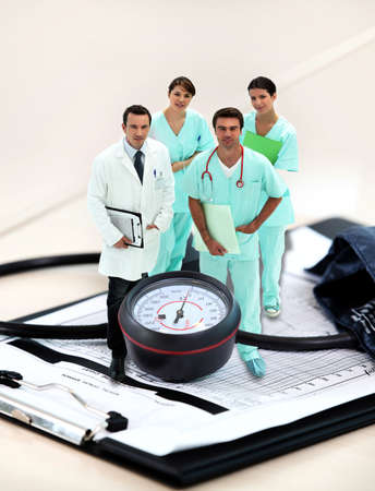 swamped: portrait of medical staff  amid giant clipboard and sphygmomanometer